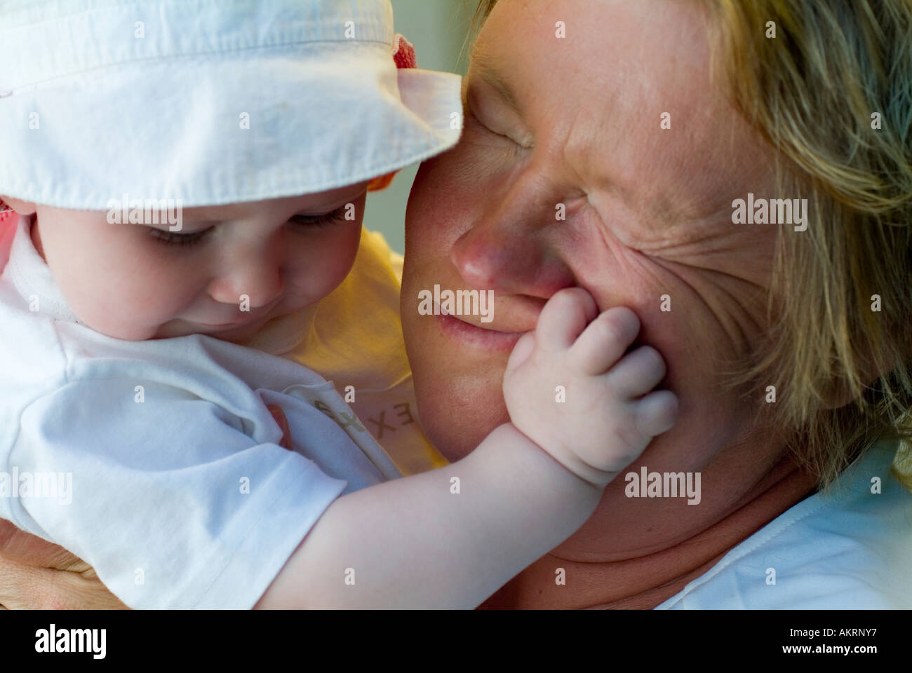 grandmother and grandchild baby of 8 months with sun hat and a woman in age of about 45 to 55 years Stock Photo