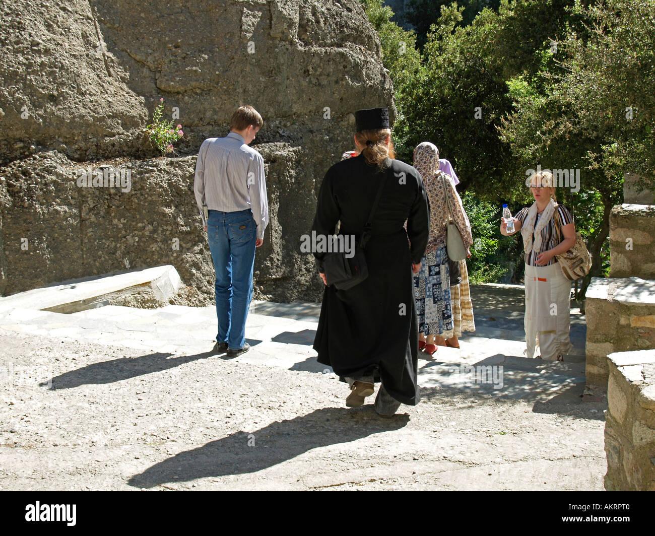 Meteora visitors and a monk on the yard of the monastery Agios Nikolaos Anapafsas Stock Photo