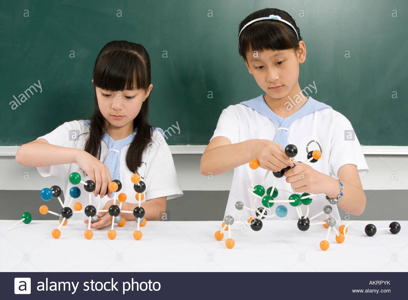 Two girls making chemistry models - Stock Image