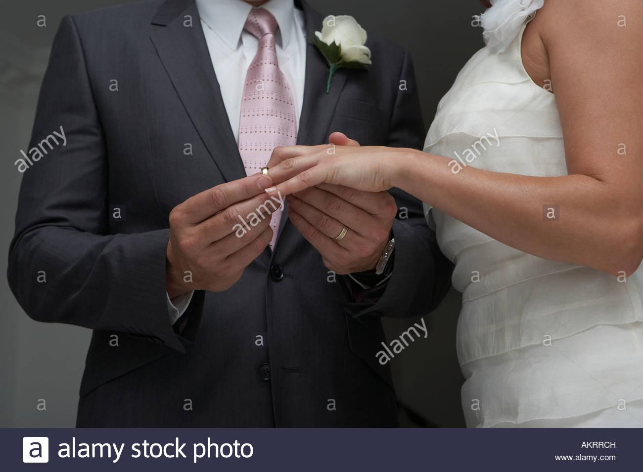 Groom putting ring on brides finger - Stock Image