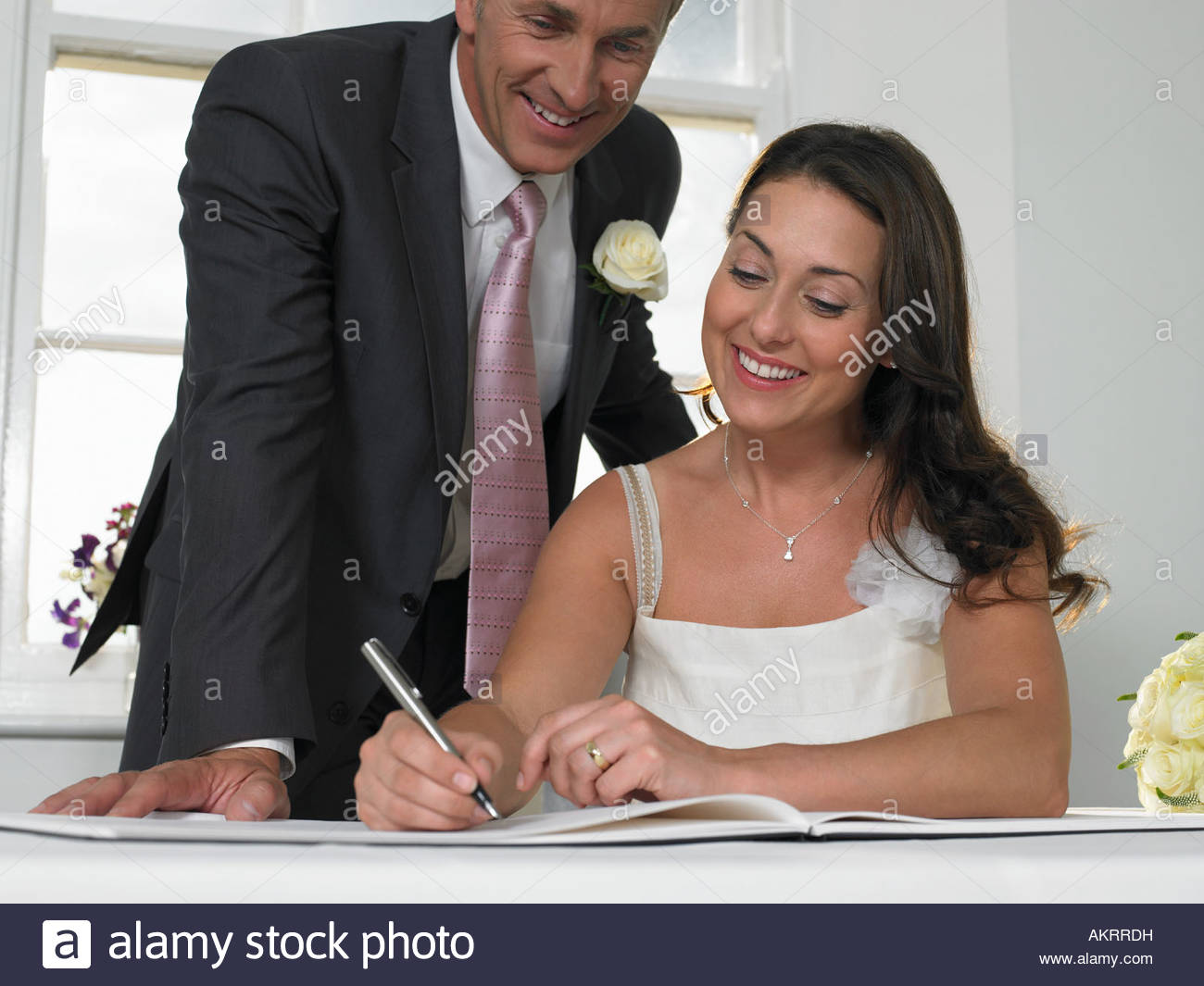 A couple signing the wedding register - Stock Image