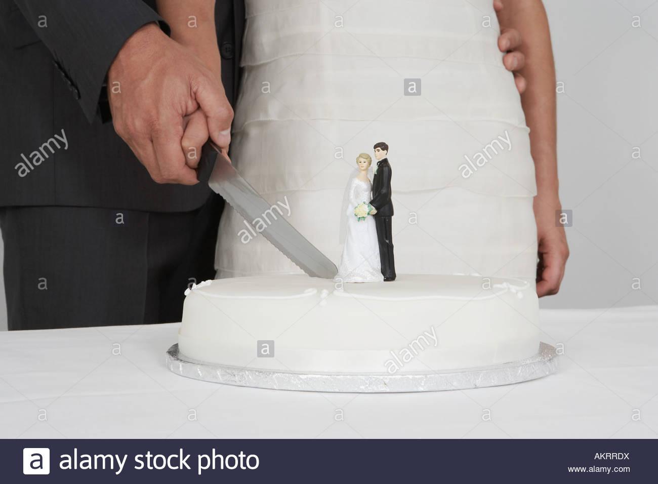 Newlyweds cutting the wedding cake - Stock Image