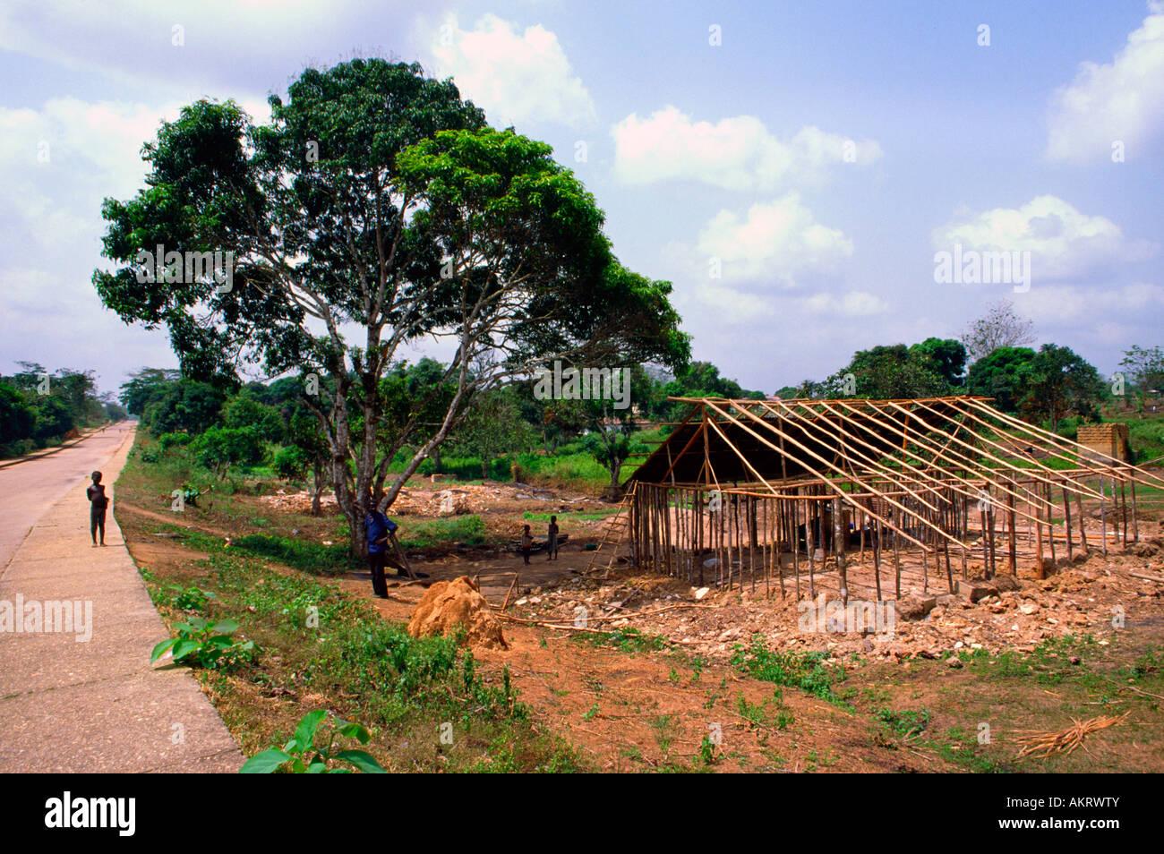 A man rebuilds a house in the aftermath of civil war in Zwedru Liberia - Stock Image