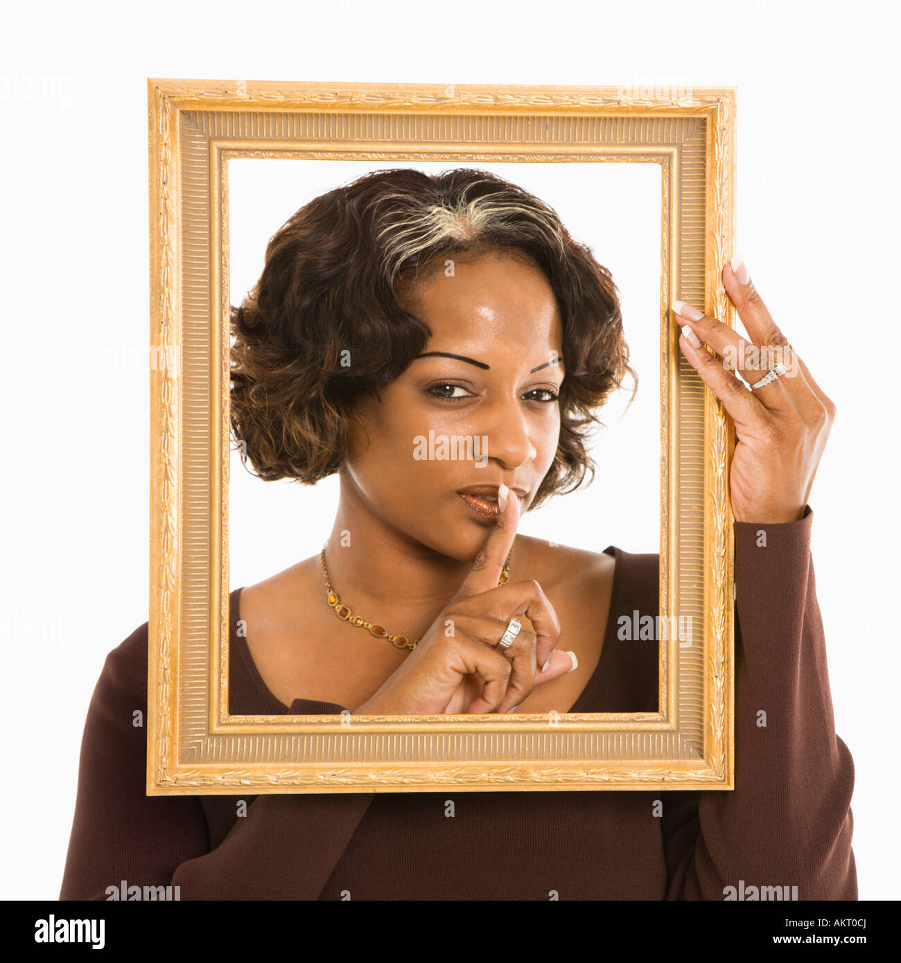 Woman holding frame around head holding finger up to lips Stock ...