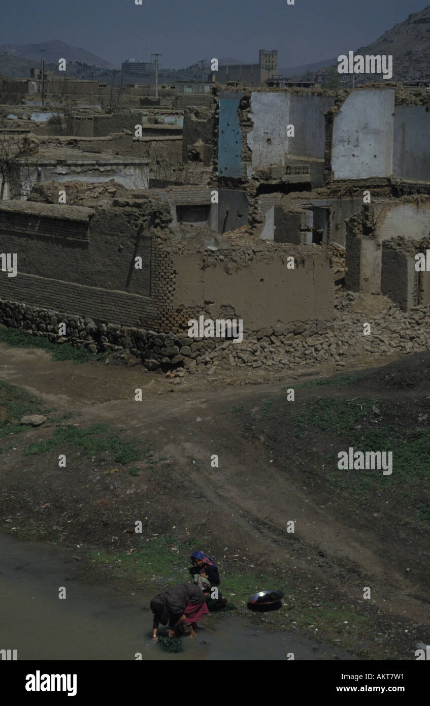 ruined homes behind river West Kabul Afghanistan - Stock Image