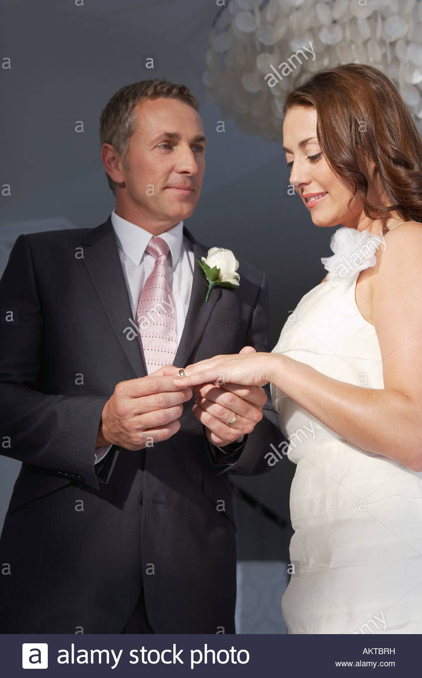 Groom putting ring on brides finger - Stock Image