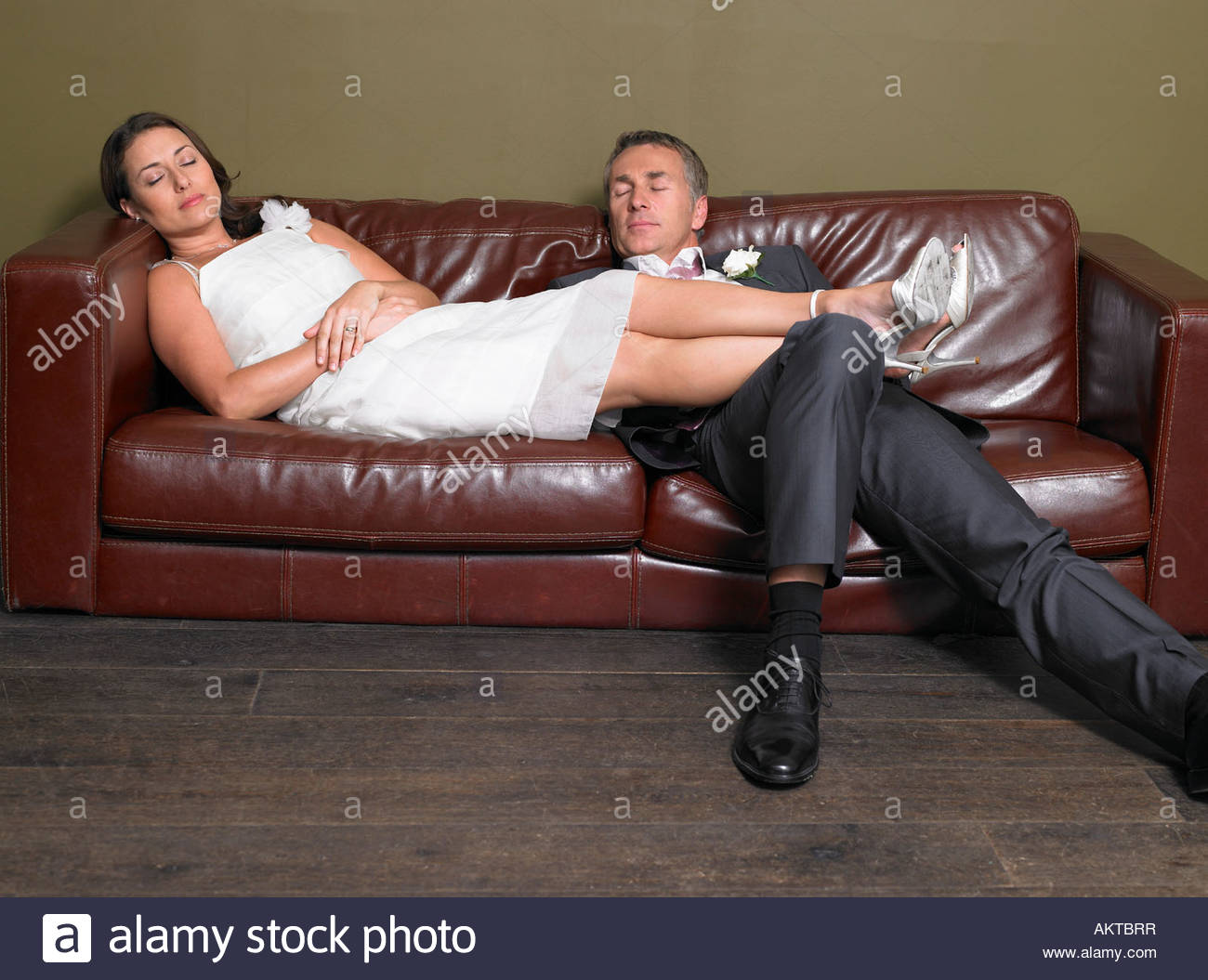 Bride and groom aslepp on a sofa - Stock Image