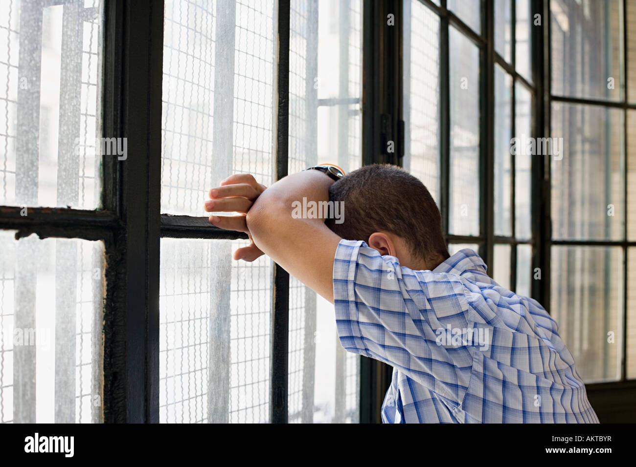 Teenage boy leaning against a window - Stock Image
