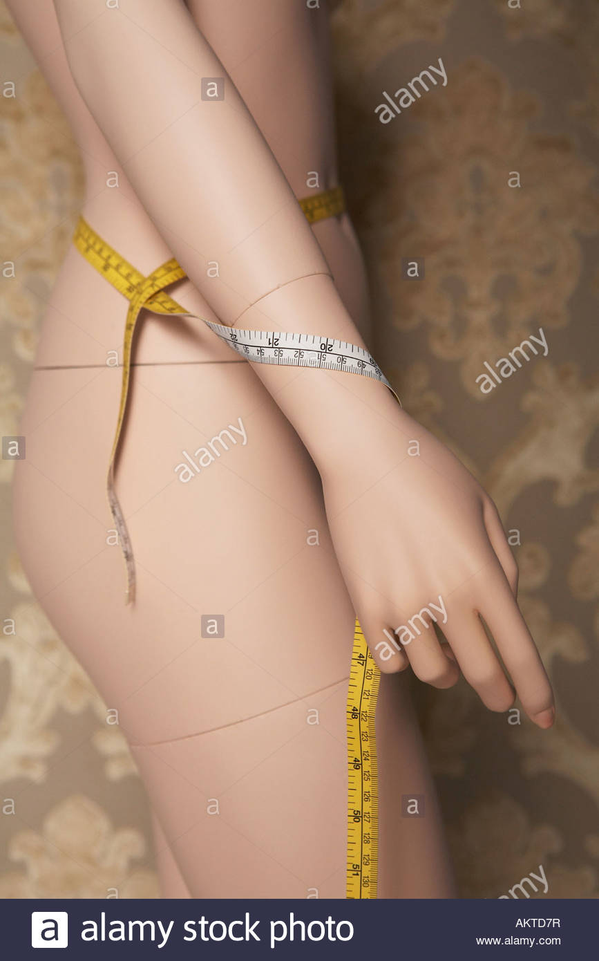Mannequin wrapped in tape measures - Stock Image