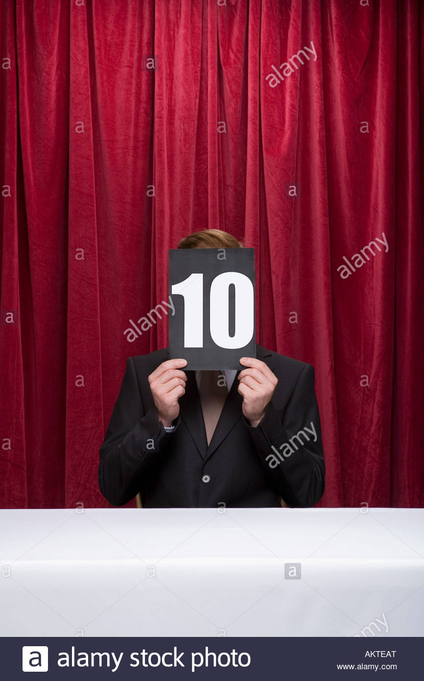 Judge with a score card covering his face - Stock Image