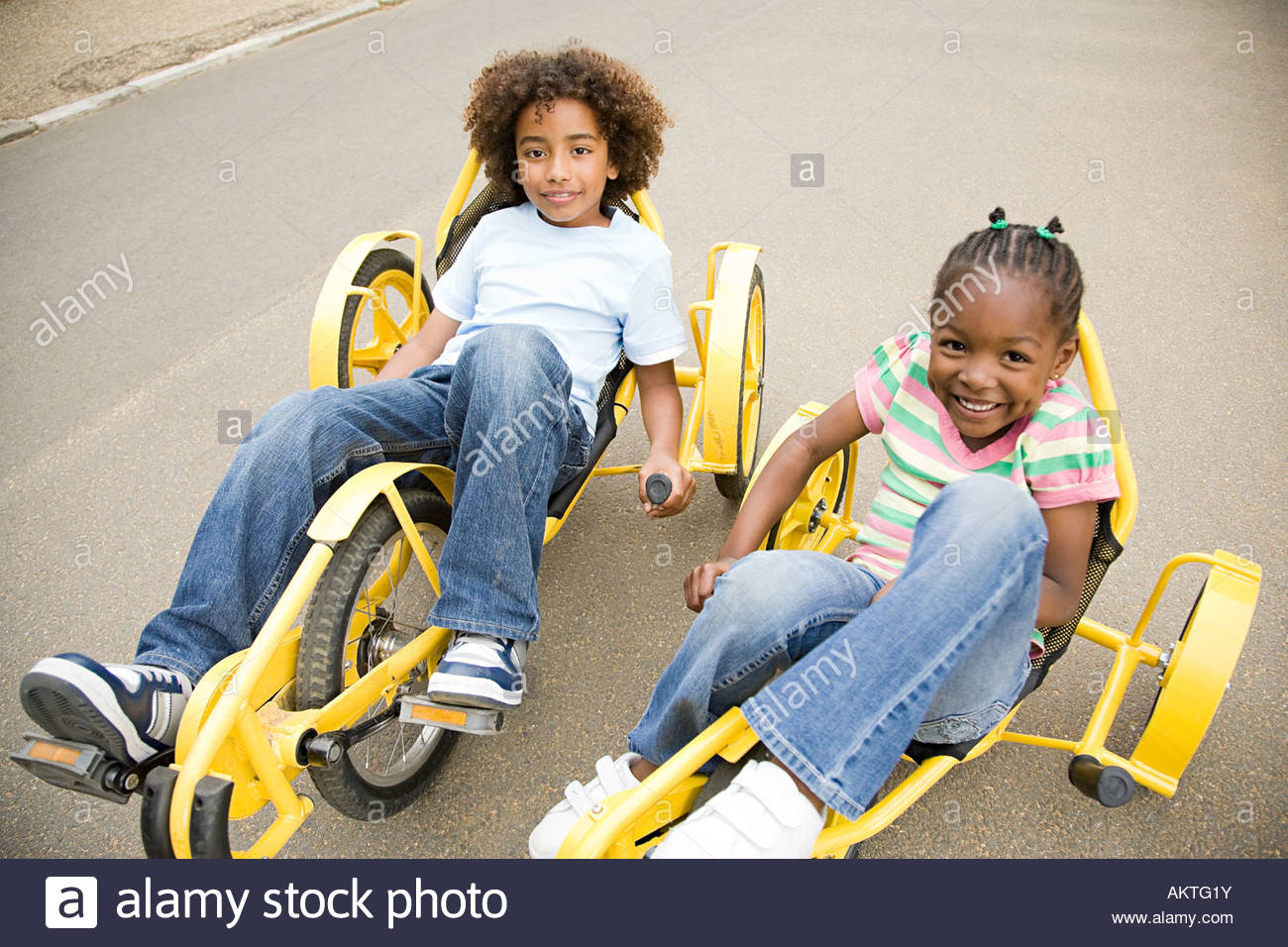 Boy and girl in tricycles - Stock Image