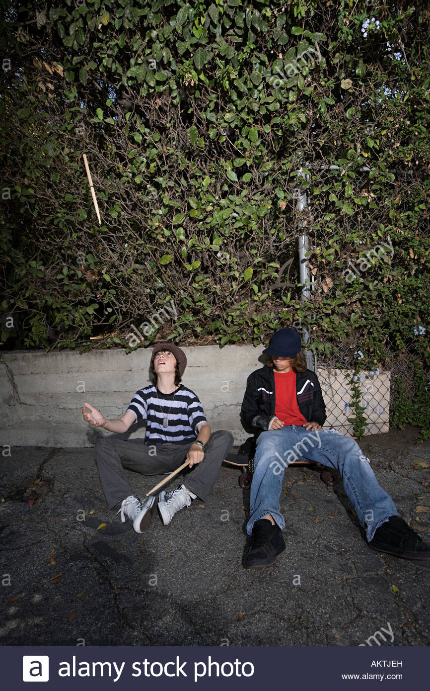 Boys sat in a street - Stock Image