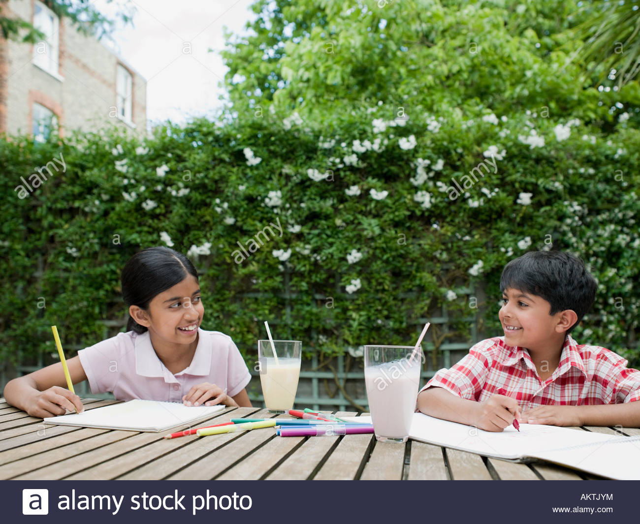 Brother and sister drawing in garden - Stock Image