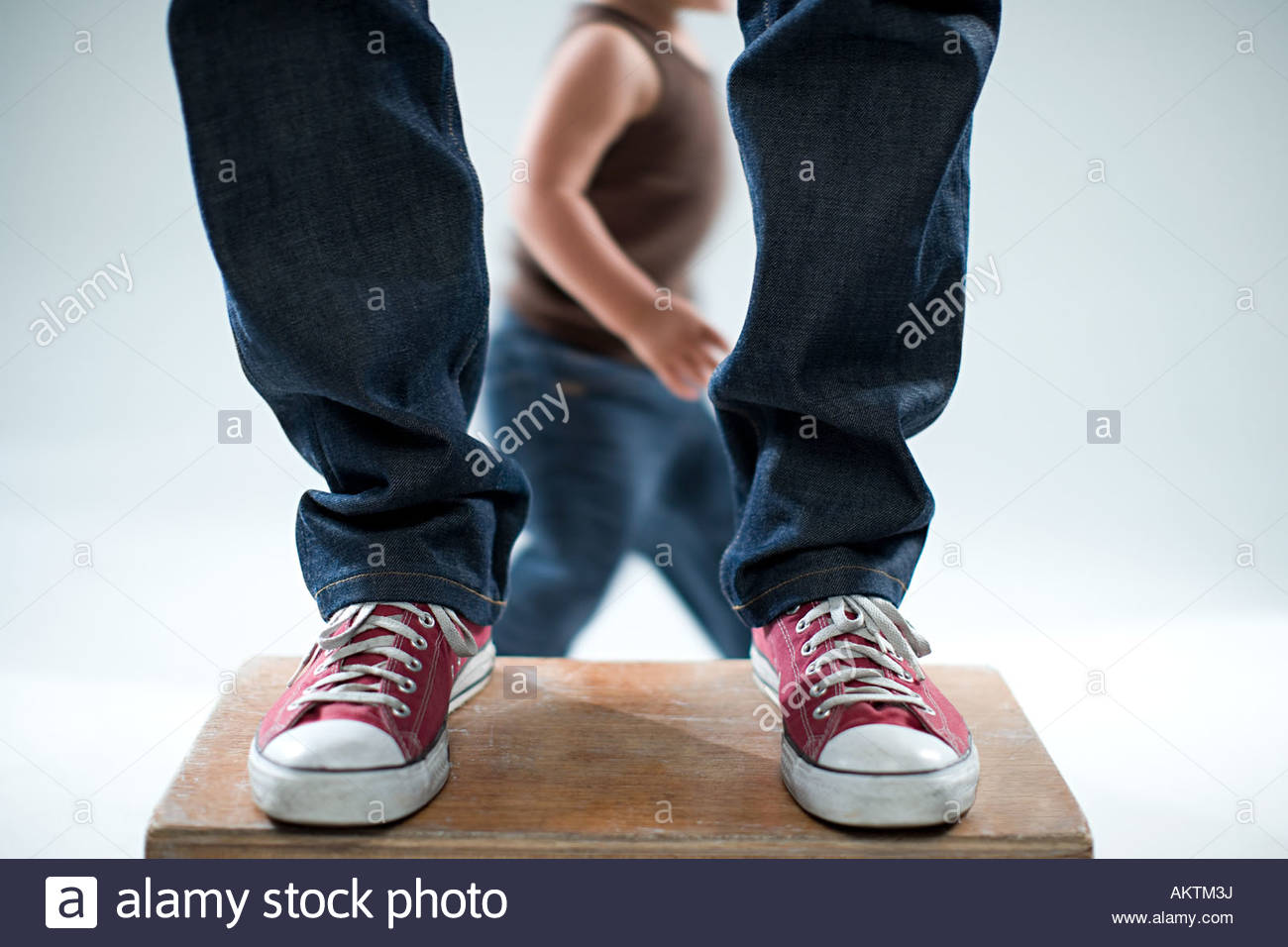 Child and legs of adult - Stock Image