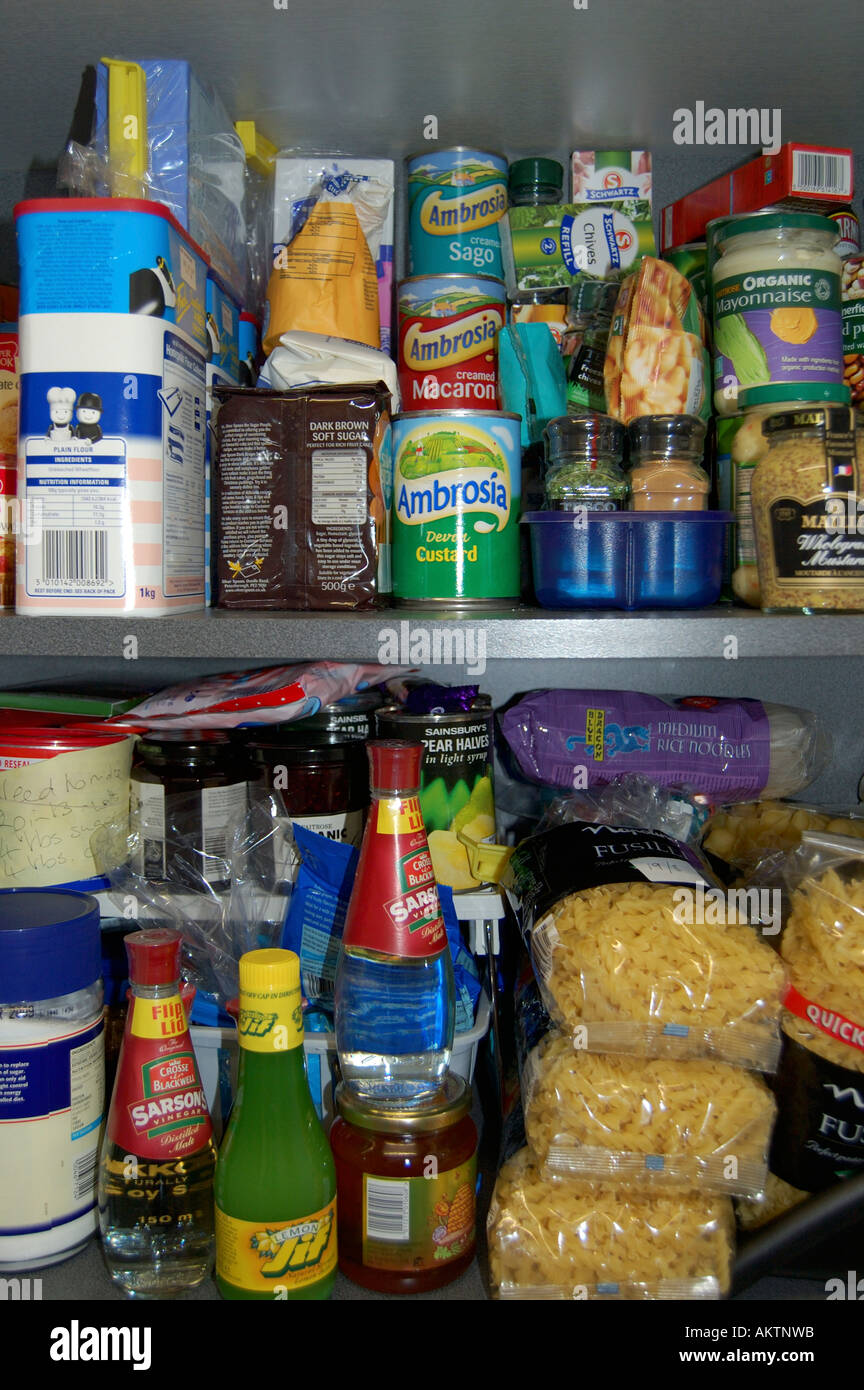 Tins and packets of food on shelves in a kitchen cupboard - Stock Image