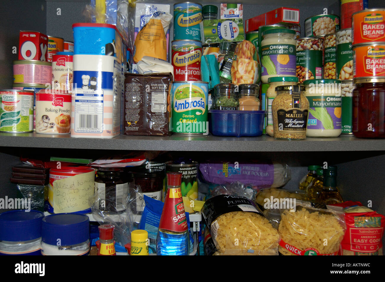Shelves in a food cupboard full of groceries - Stock Image