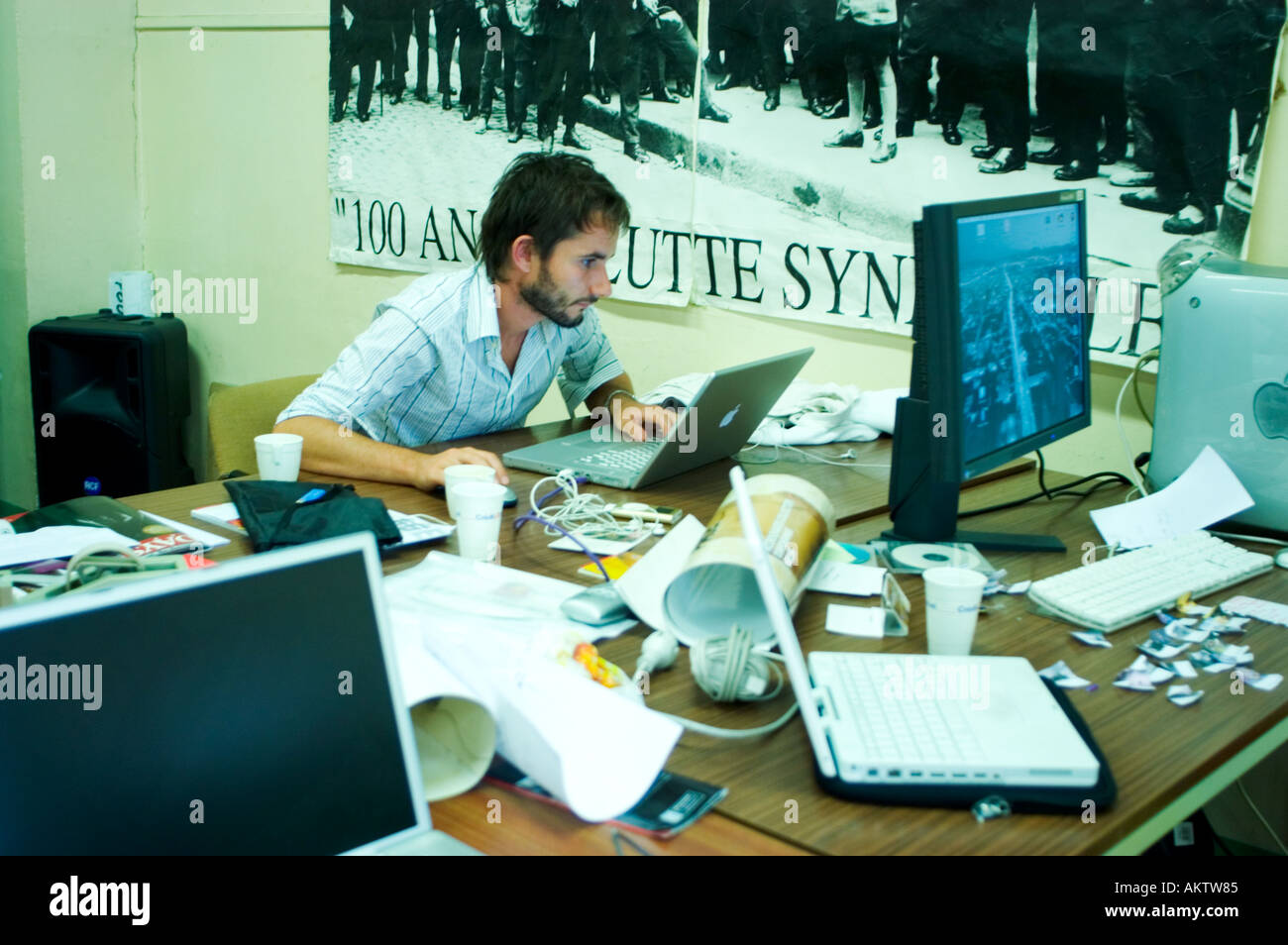 Perpignan France, Young Man Working, Looking at Apple Computer Screen at Messy Desk,  international communication - Stock Image