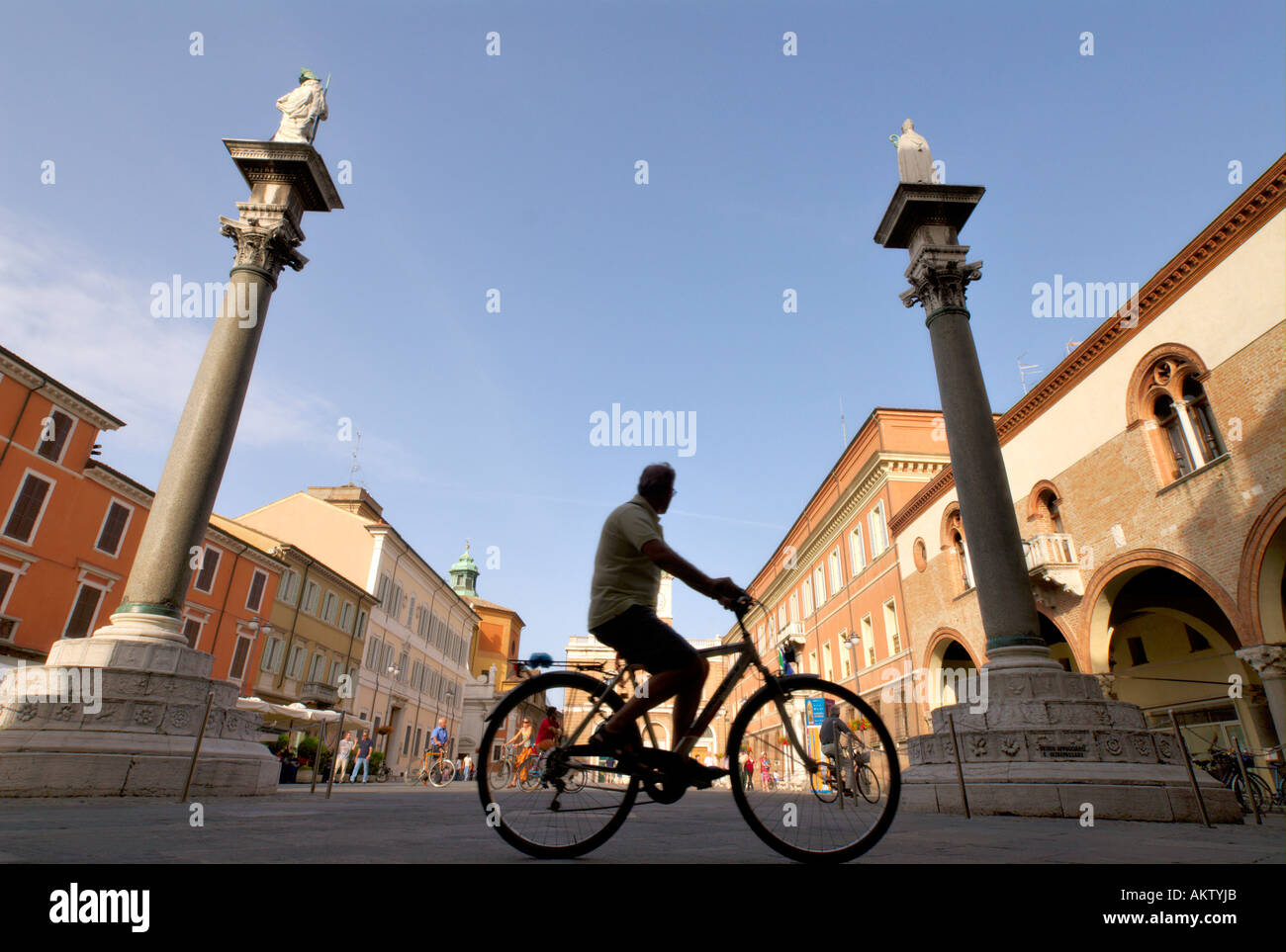 Ravenna Italy Cyclist rides through Piazza del Popolo framed by the Venetian columns - Stock Image