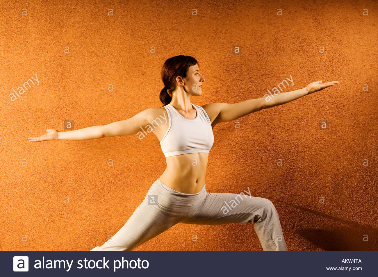 Adult woman in Yoga like stretch pose looking forward wtih palms up strength beauty balance and  grace - Stock Image