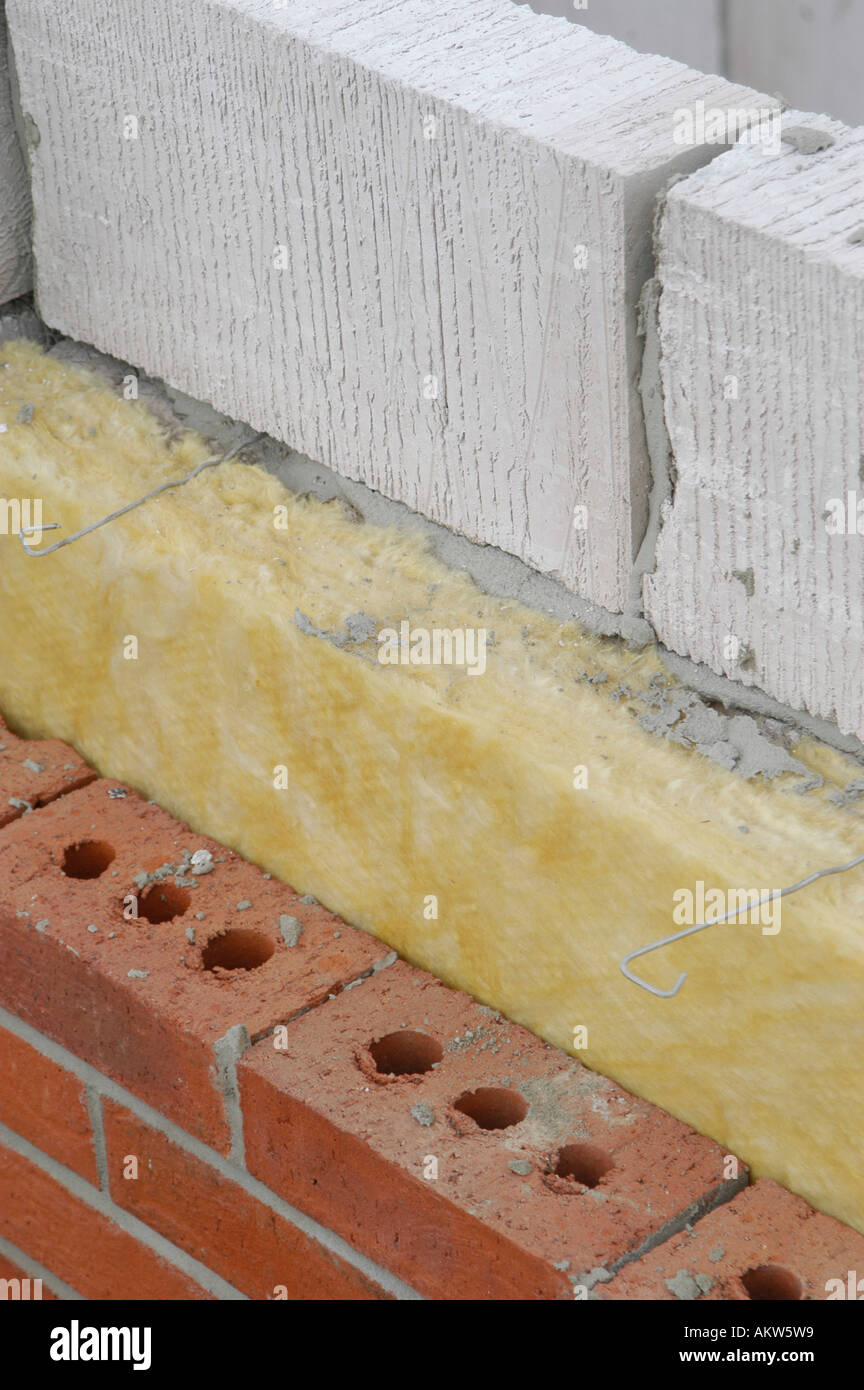 Part Of A New House Under Construction Showing The Layers Of Breeze Block,  Insulation And Bricks