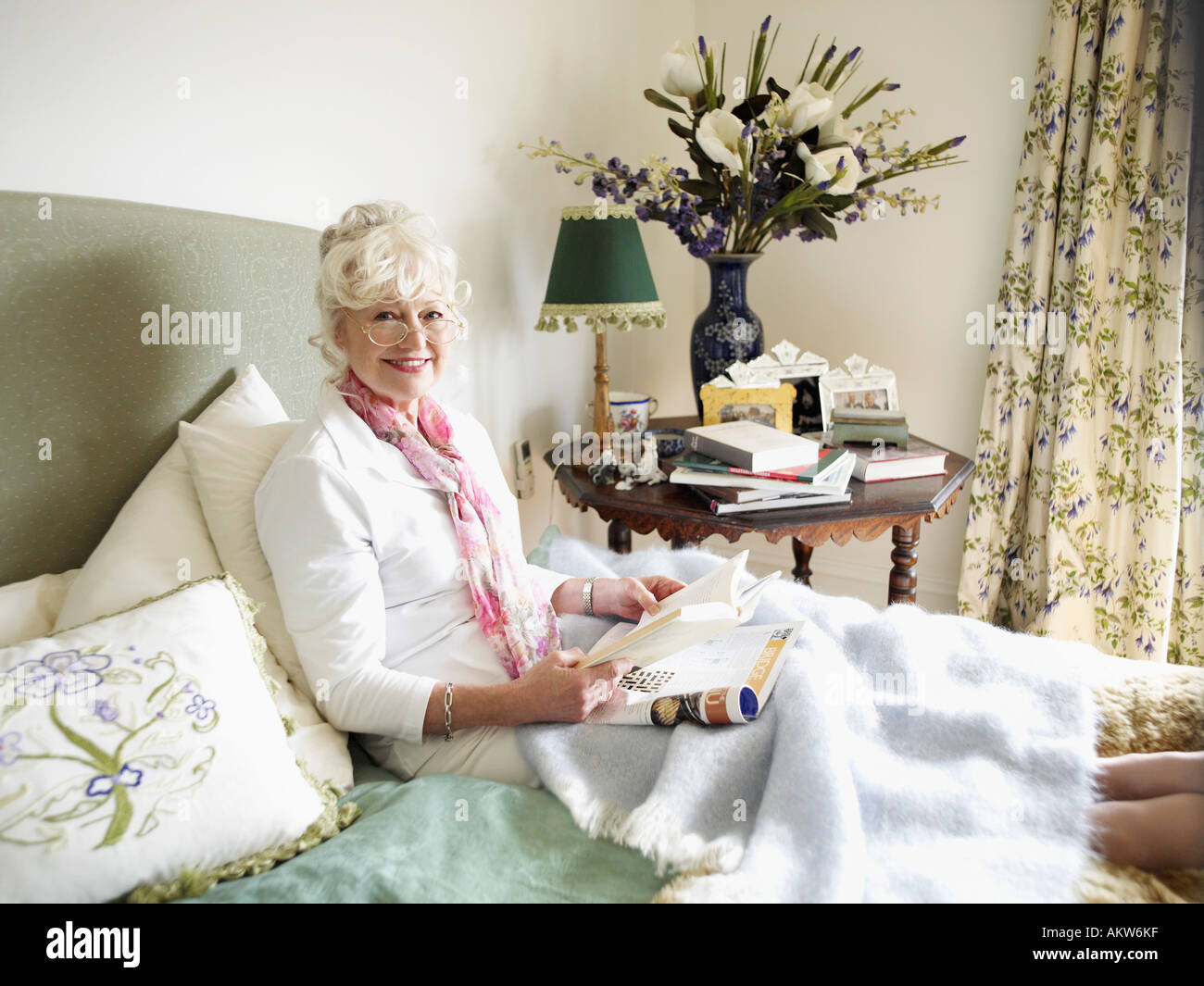 Senior woman sitting on bed, reading book Stock Photo
