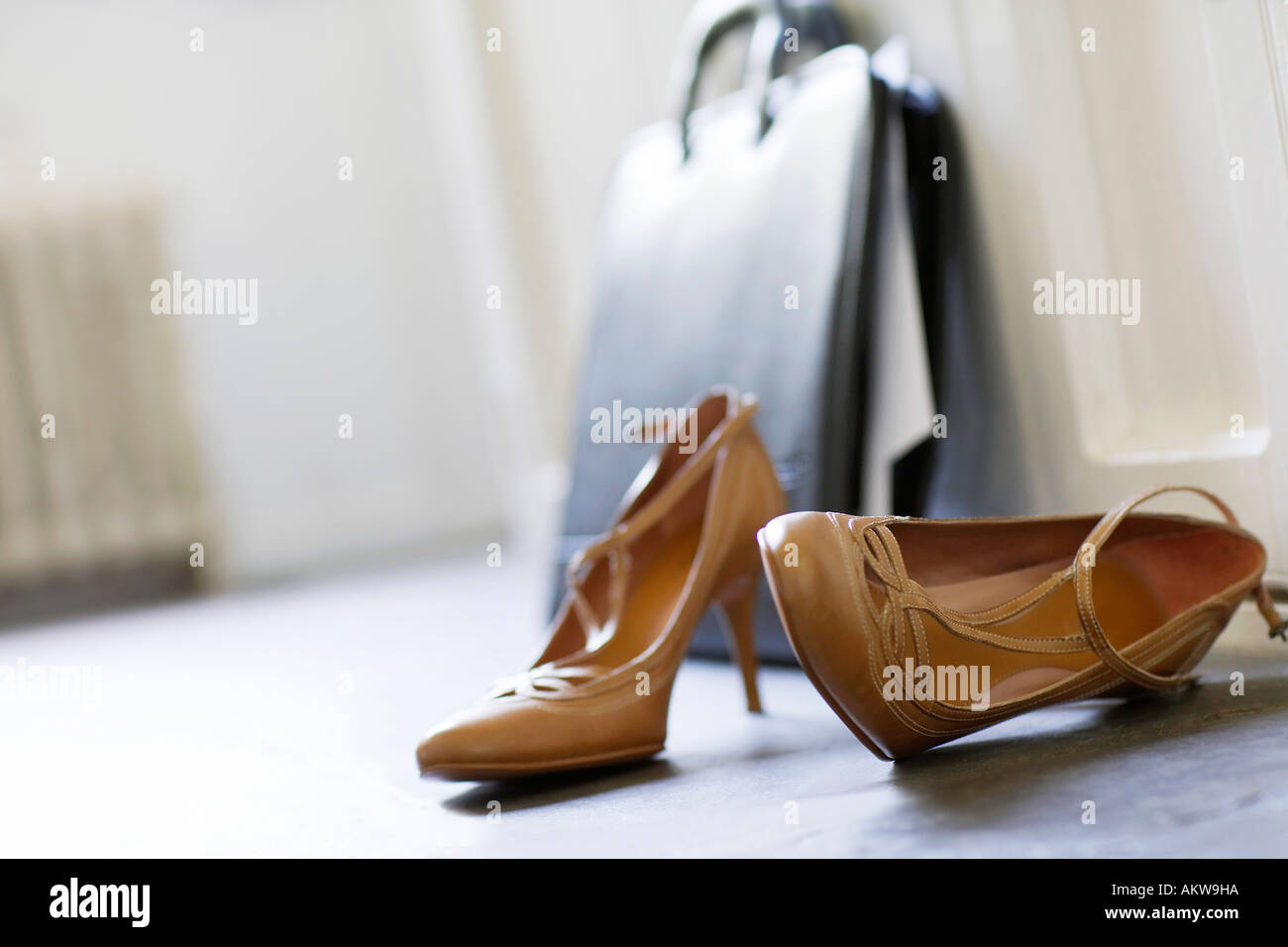 High heels and briefcase on domestic hallway floor, close up - Stock Image