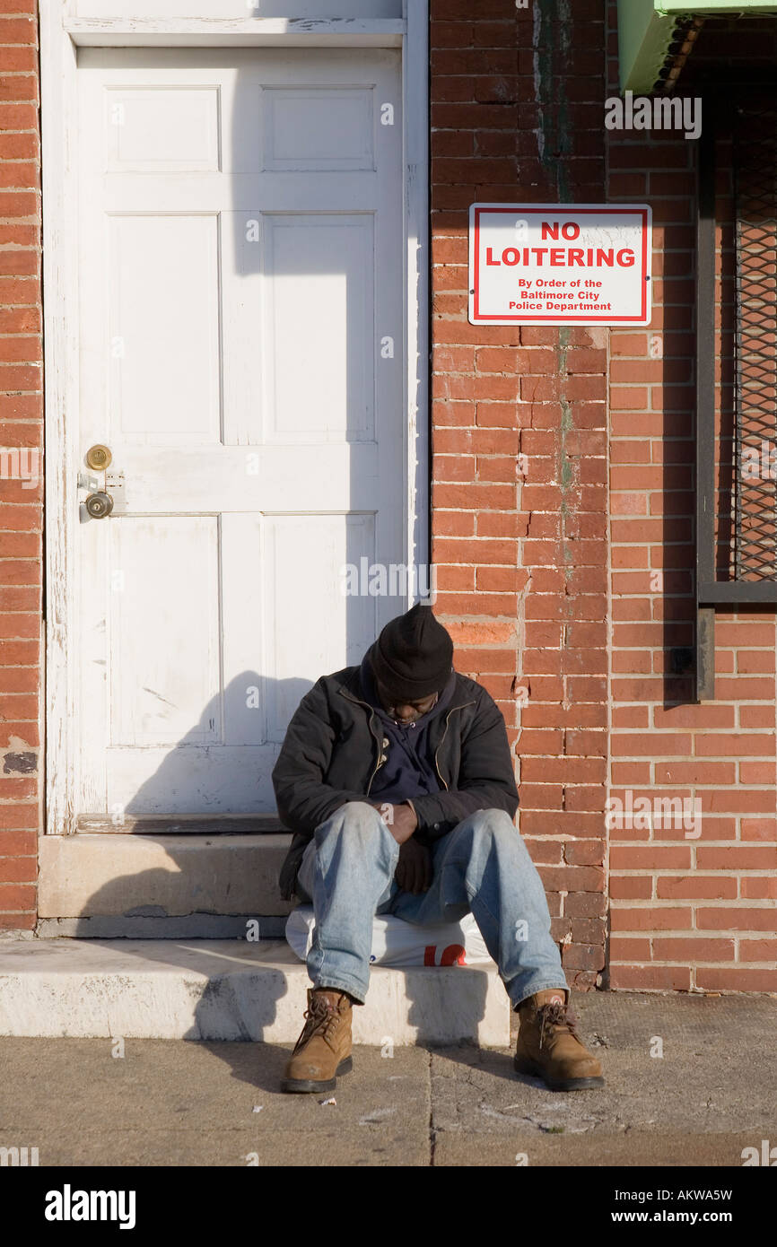 Black Afro American man under no loitering sign Baltimore Maryland - Stock Image