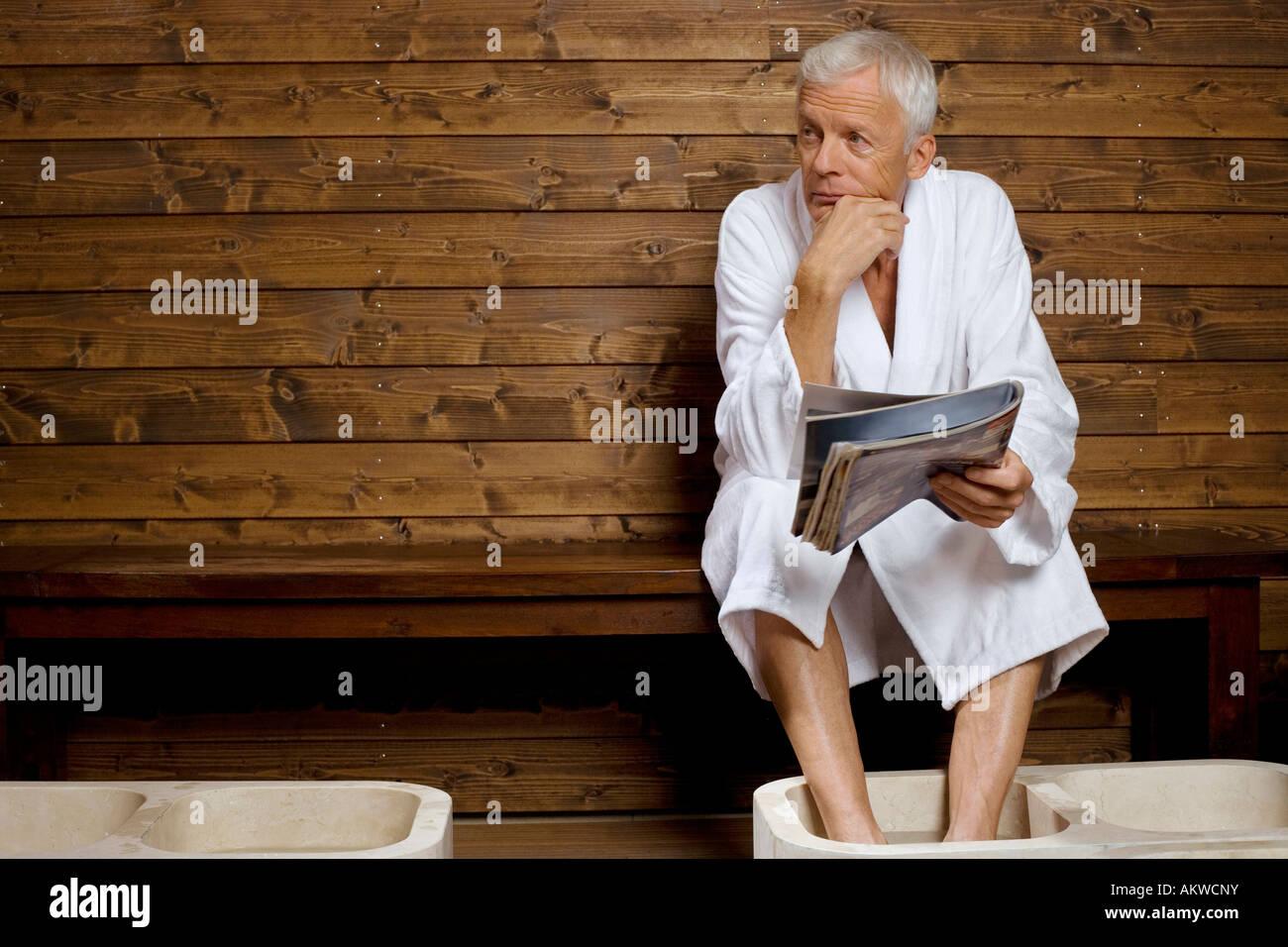 Germany, senior man having foot bath in health spa - Stock Image