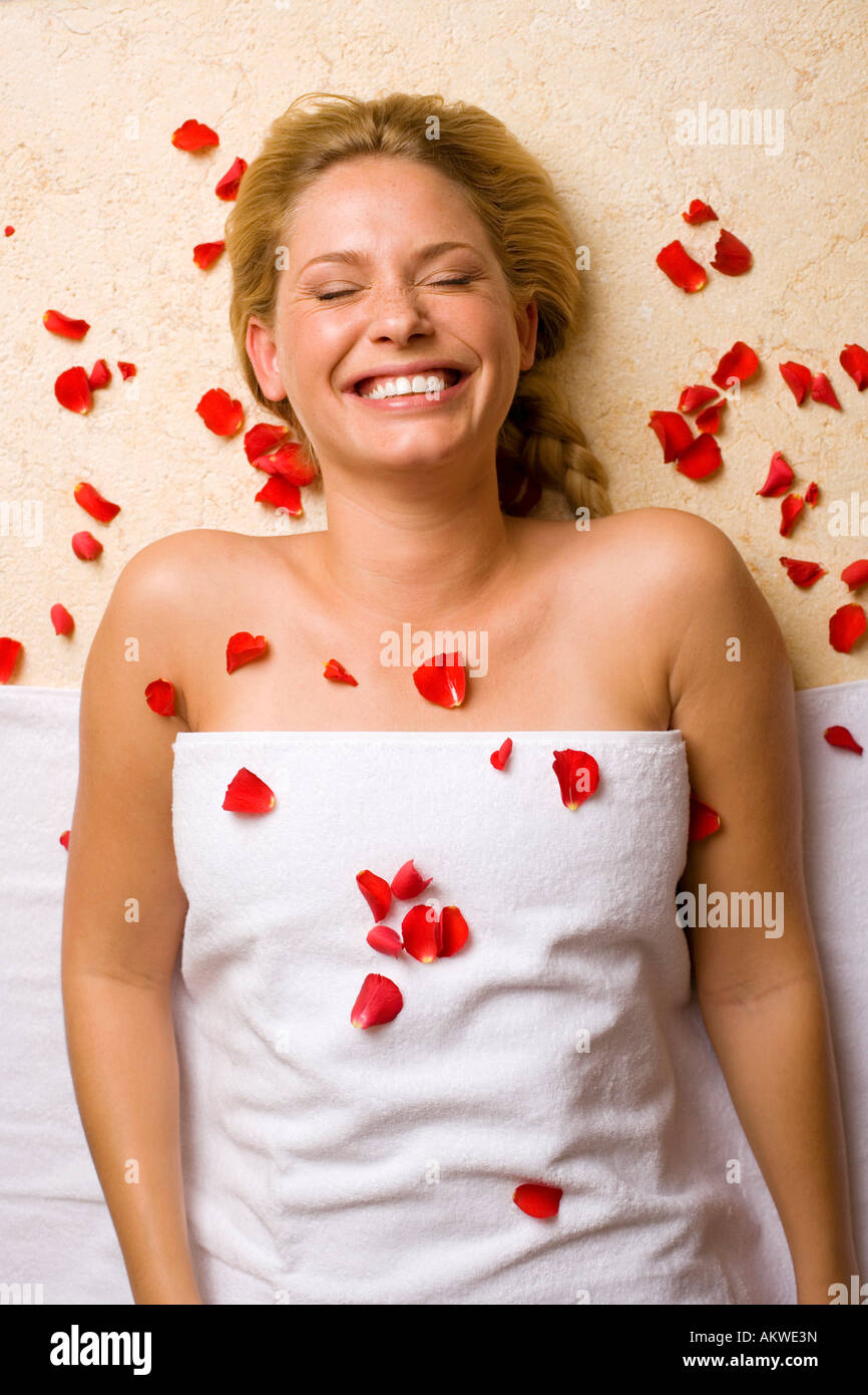 Germany, young woman lying on massage table, petals on chest - Stock Image