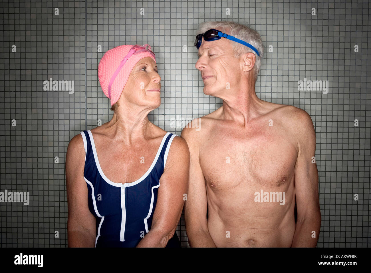 Senior couple in changing room, wearing swim cap and goggles - Stock Image