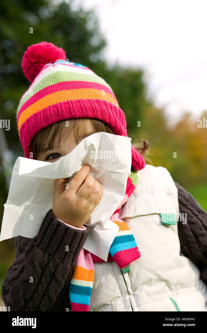 Girl (4-5) blowing nose, close-up - Stock Image
