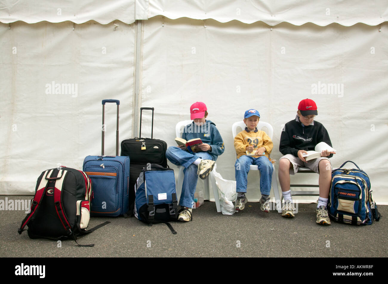 Three children wait with their bags during a strike at Heathrow Terminal Four London UK 2005 - Stock Image