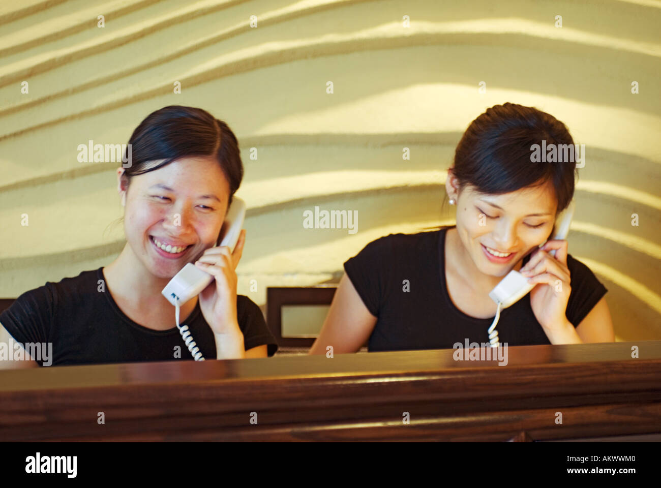 Two Asian Young Women Receptionists On Phones At Spa Reception Desk Taipei Taiwan China - Stock Image