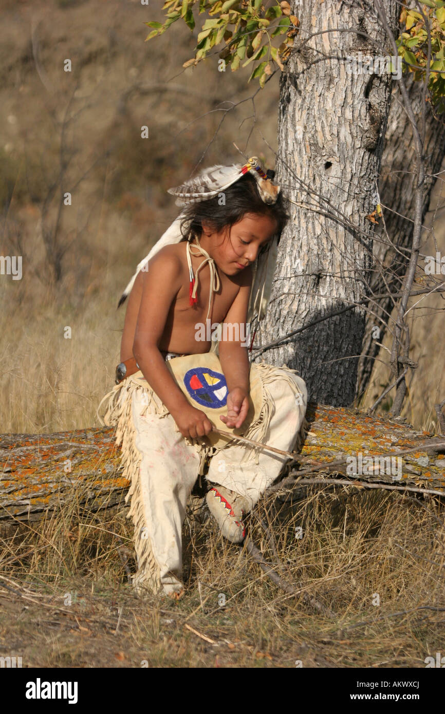 A young Native American Indian boy sitting on a log - Stock Image