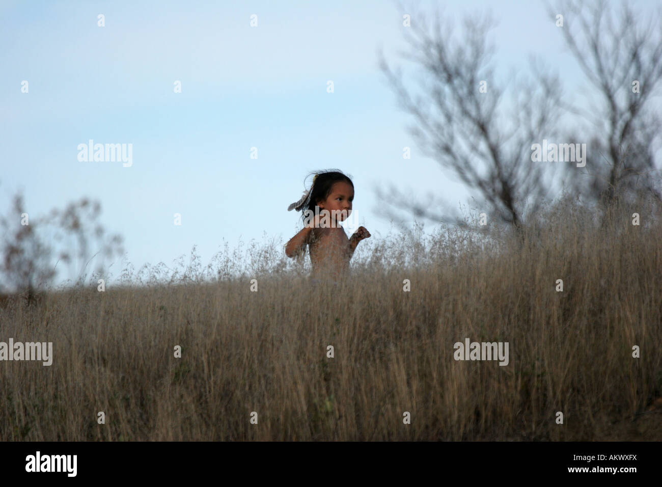 A Native American Indian boy running in the dried grasses - Stock Image