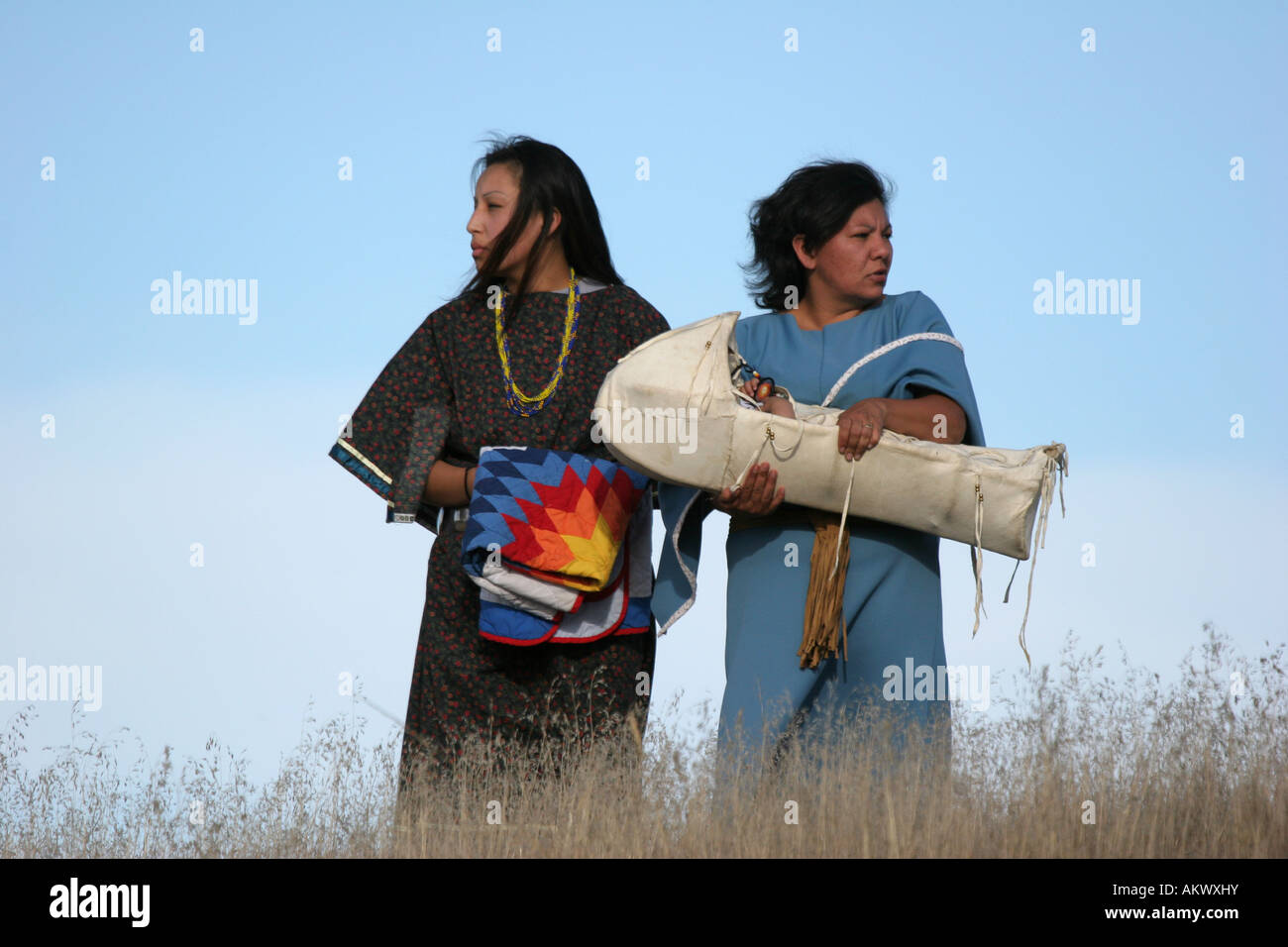 Two young ladies on top of a hill holding a blanket and a baby in a cradle - Stock Image