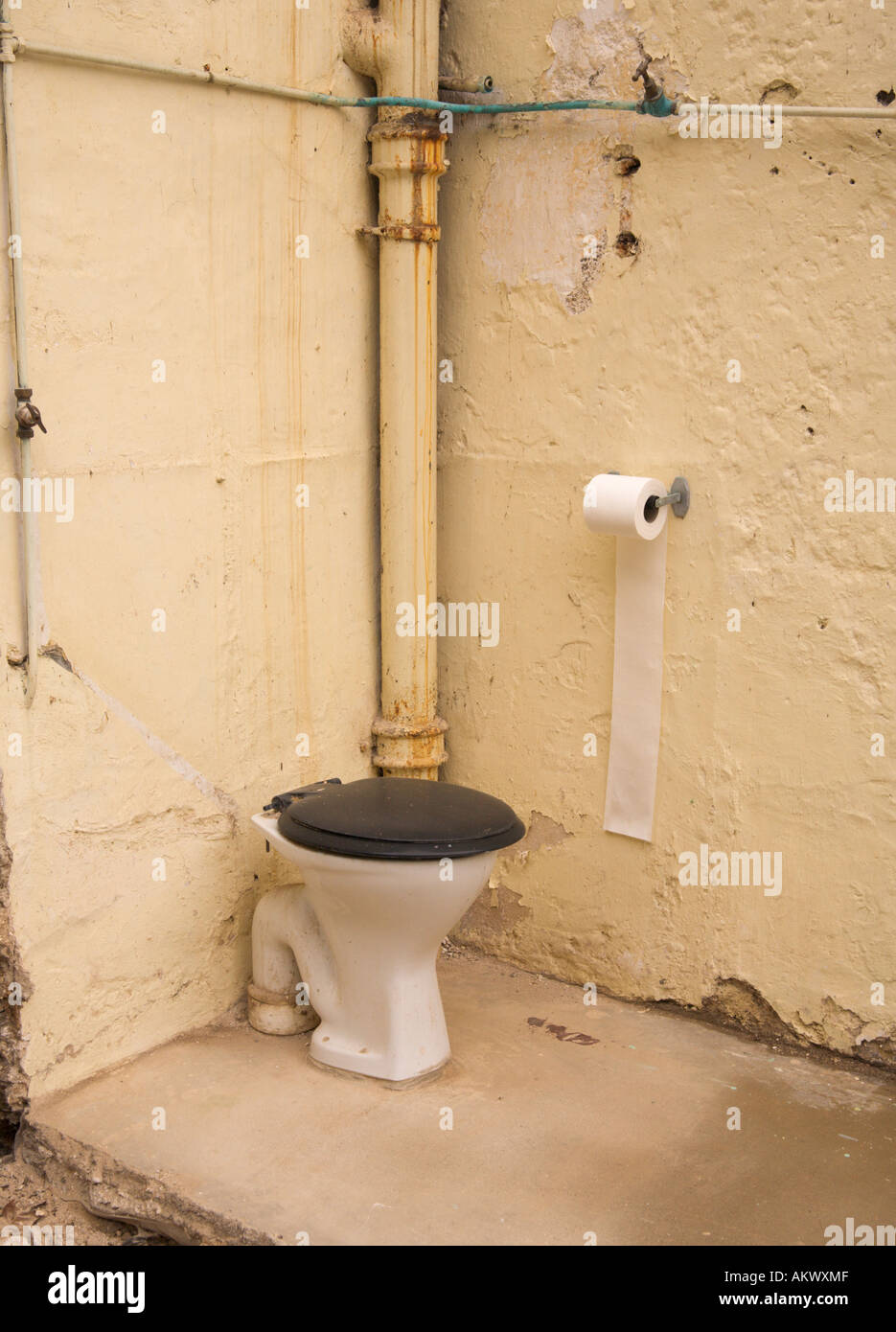 Corner of an old outdoor toilet half demolished with only two walls left standing in Braunton Village Devon England - Stock Image