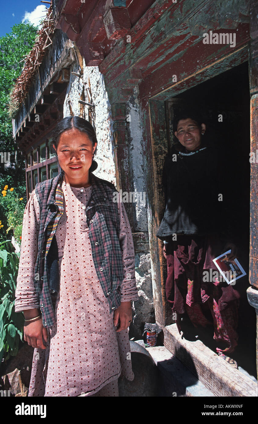 Ladakhi women standing outside and in the doorway of their home Chojti village Indus valley Ladakh Jammu Kashmir State Northern - Stock Image