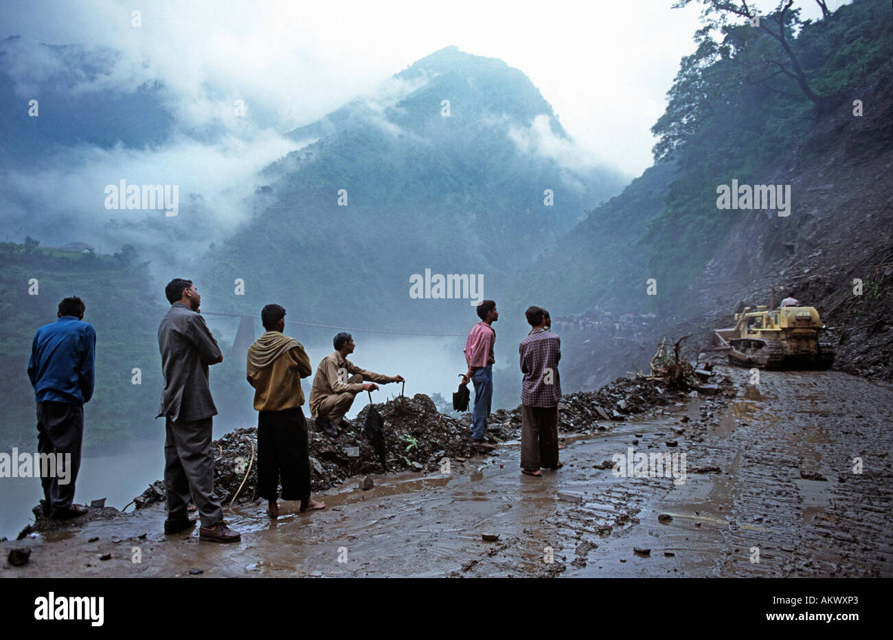 A devastating landslide has swept the road away. A bulldozer attempts to reconnect the highway from Manali to Delhi. Himachal P - Stock Image