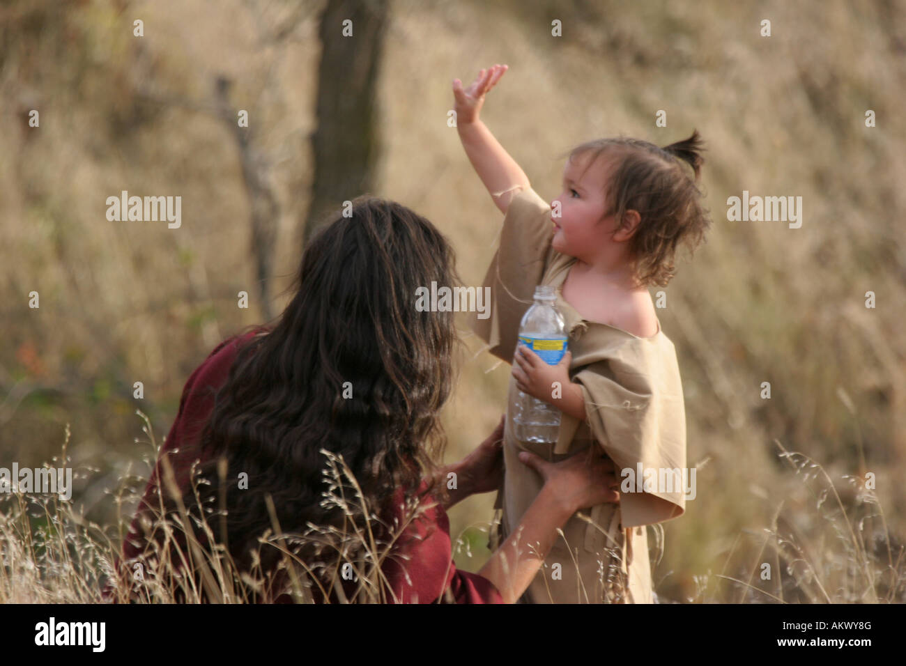 A Native American Indian mother and her daughter sitting outside having a picnic waving to friends - Stock Image