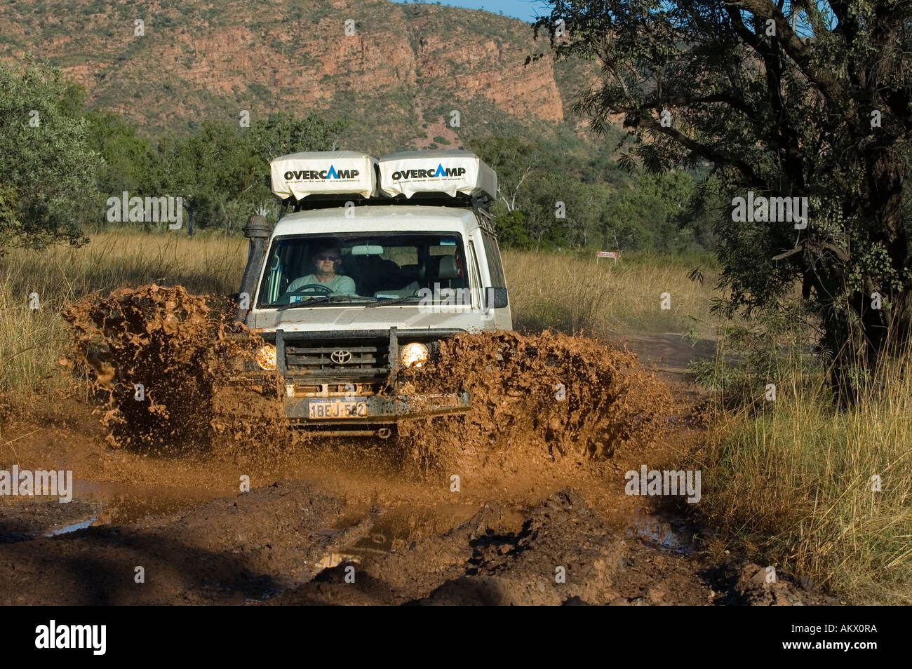 Offroad vehicle driving through mud, Gibb Road, Northern Territory, Australia - Stock Image