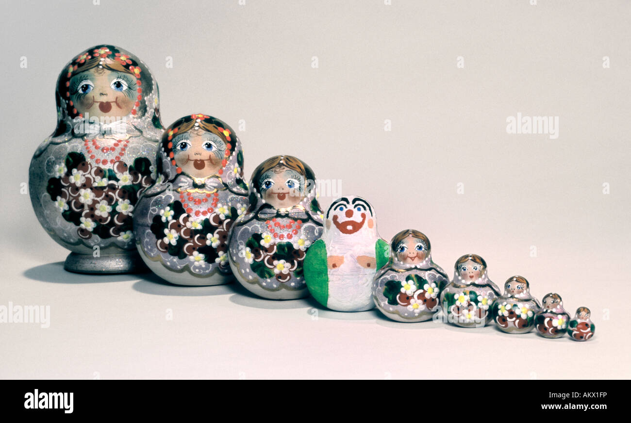 Russian Dolls with a Deviant, straight line, white background. - Stock Image