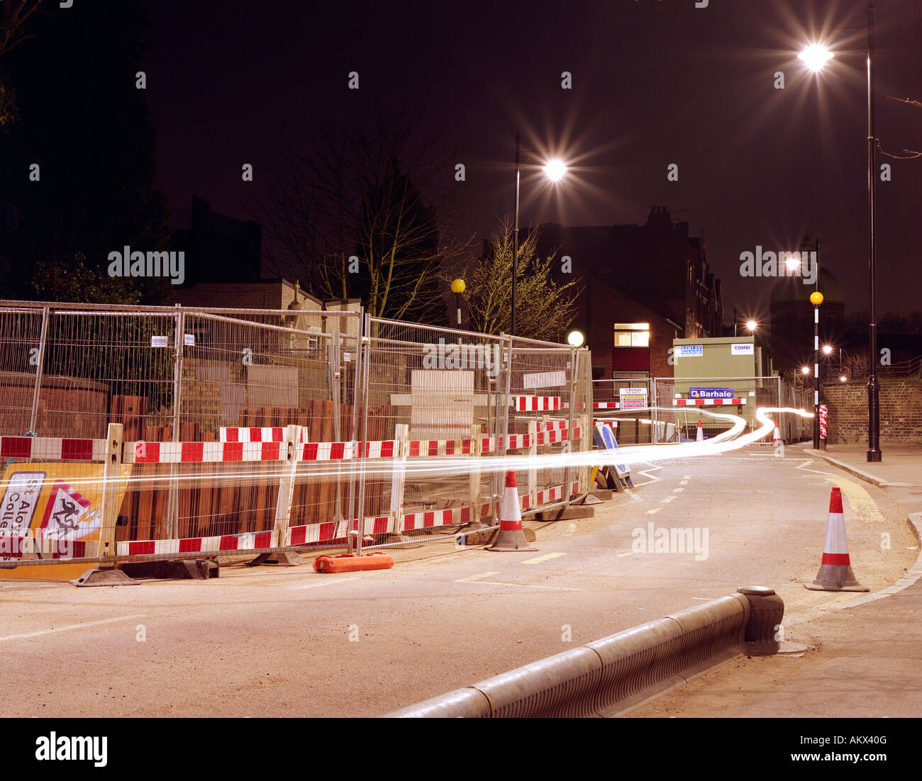 Light Trails from Two Scooters Passing Road Works on a Street Closed to Cars - Stock Image