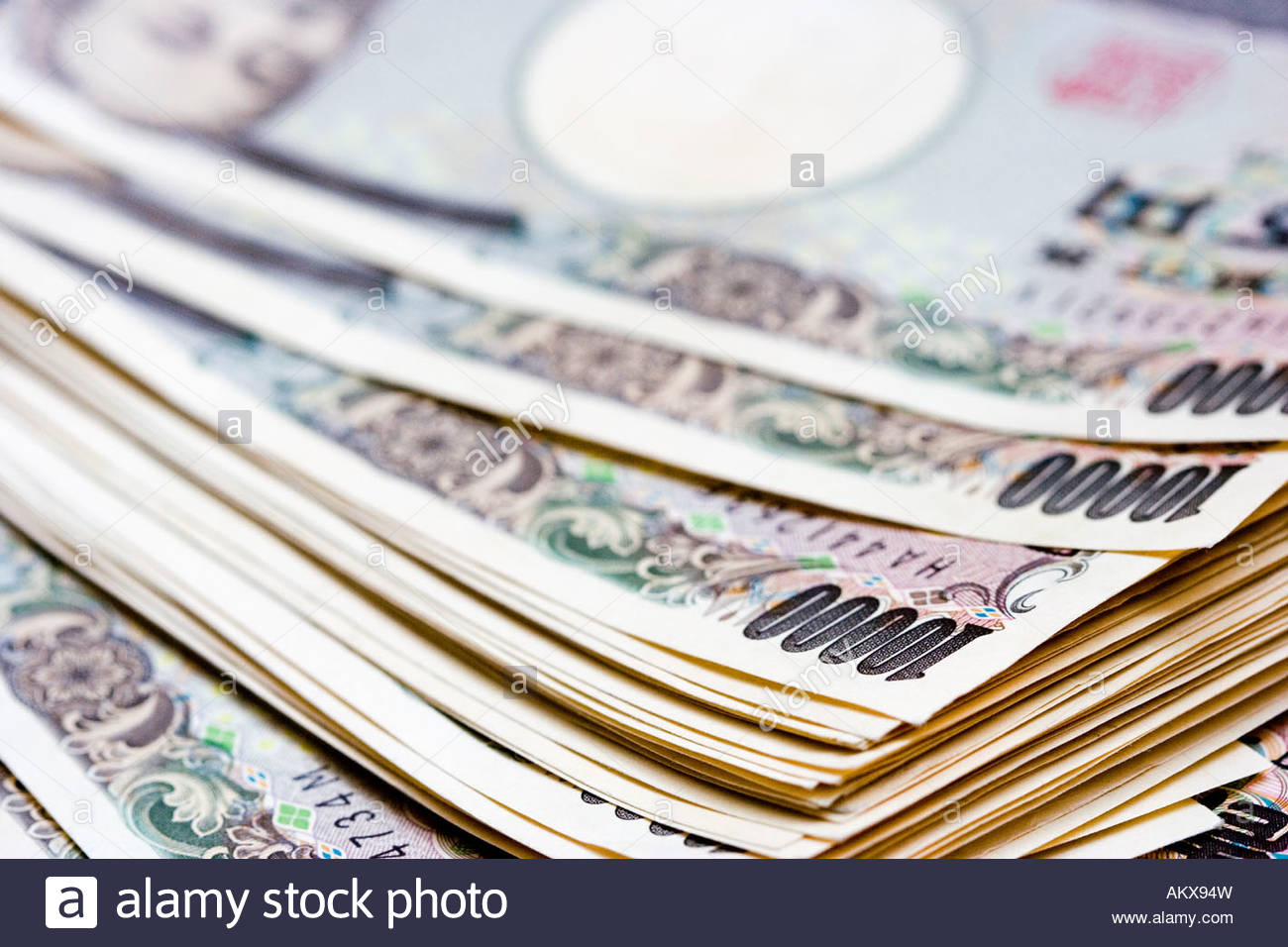 pile of Japanese 10,000 yen notes, on top of each other, shallow focus, mainly showing corner and the 10,000 symbol - Stock Image