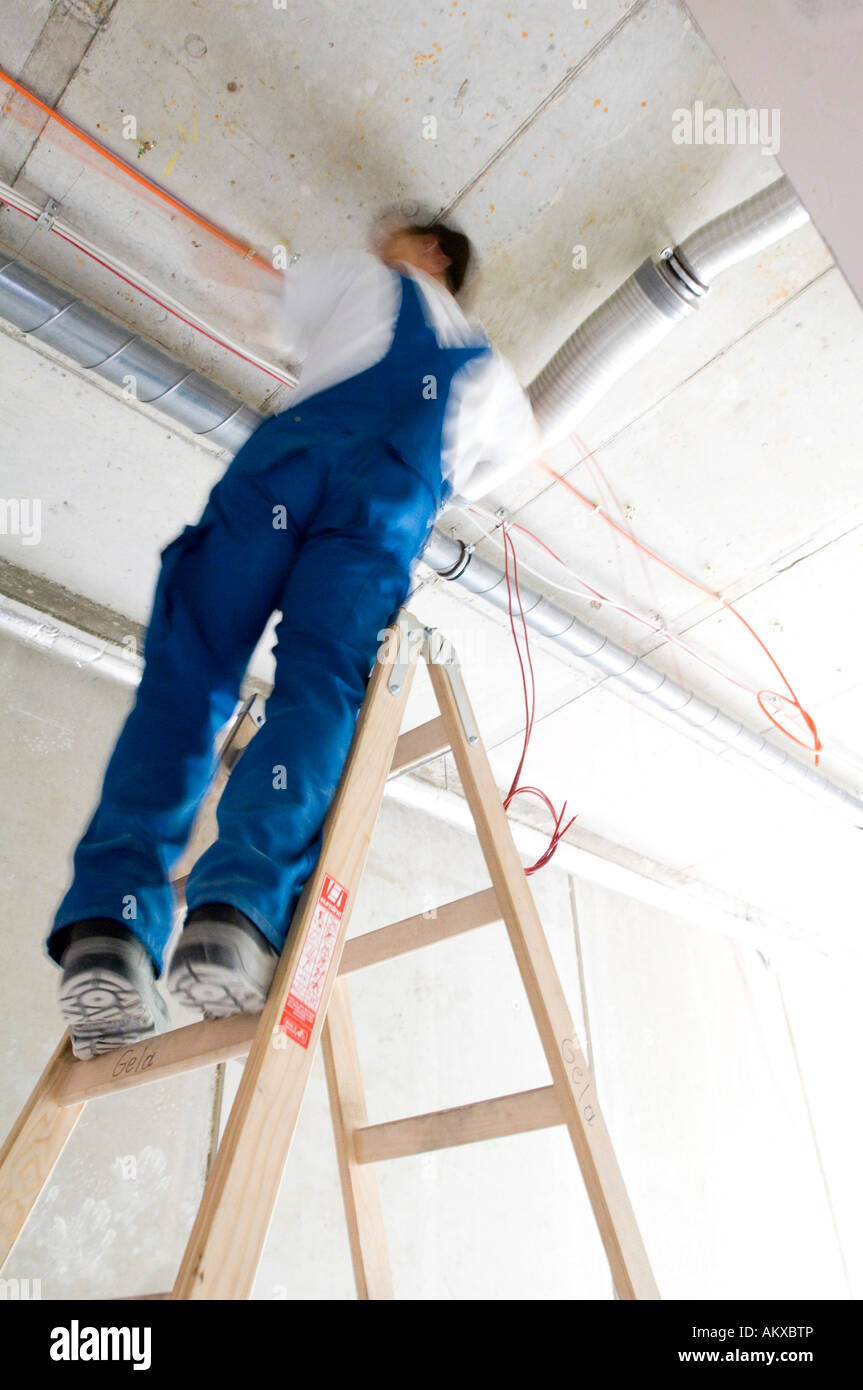 Construction worker lays cables at the ceiling Stock Photo