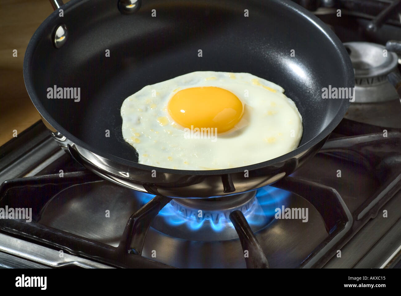 Frying an Egg in a Teflon Coated Pan - Stock Image