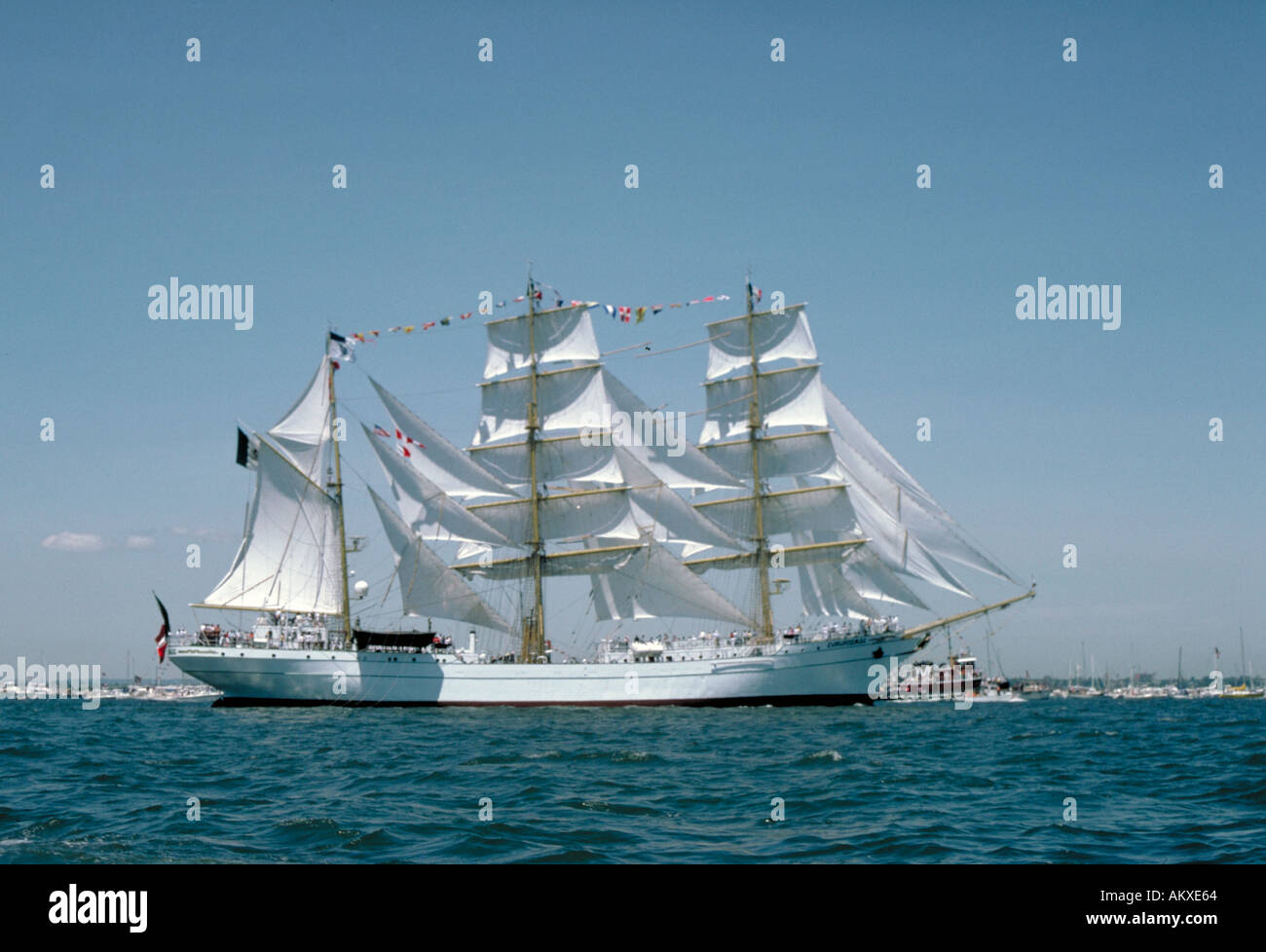 A white three masted full rigged ship with colorful flags waving in the breeze at the Tall Ships exhibition. - Stock Image
