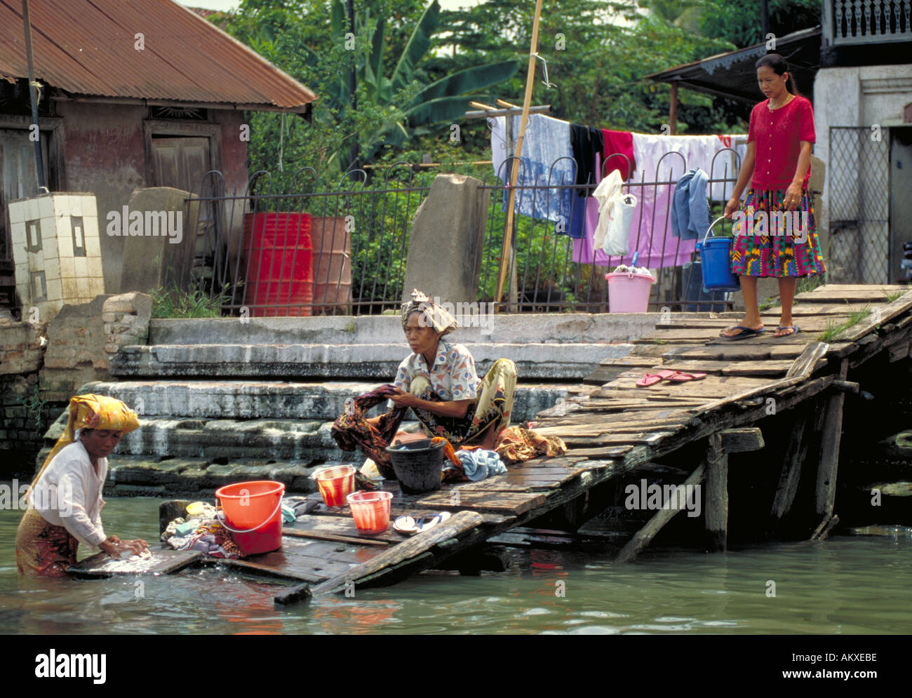 Families in Palembang Indonesia wash clothes in the Musi River. Living conditions along the river are crowded. - Stock Image