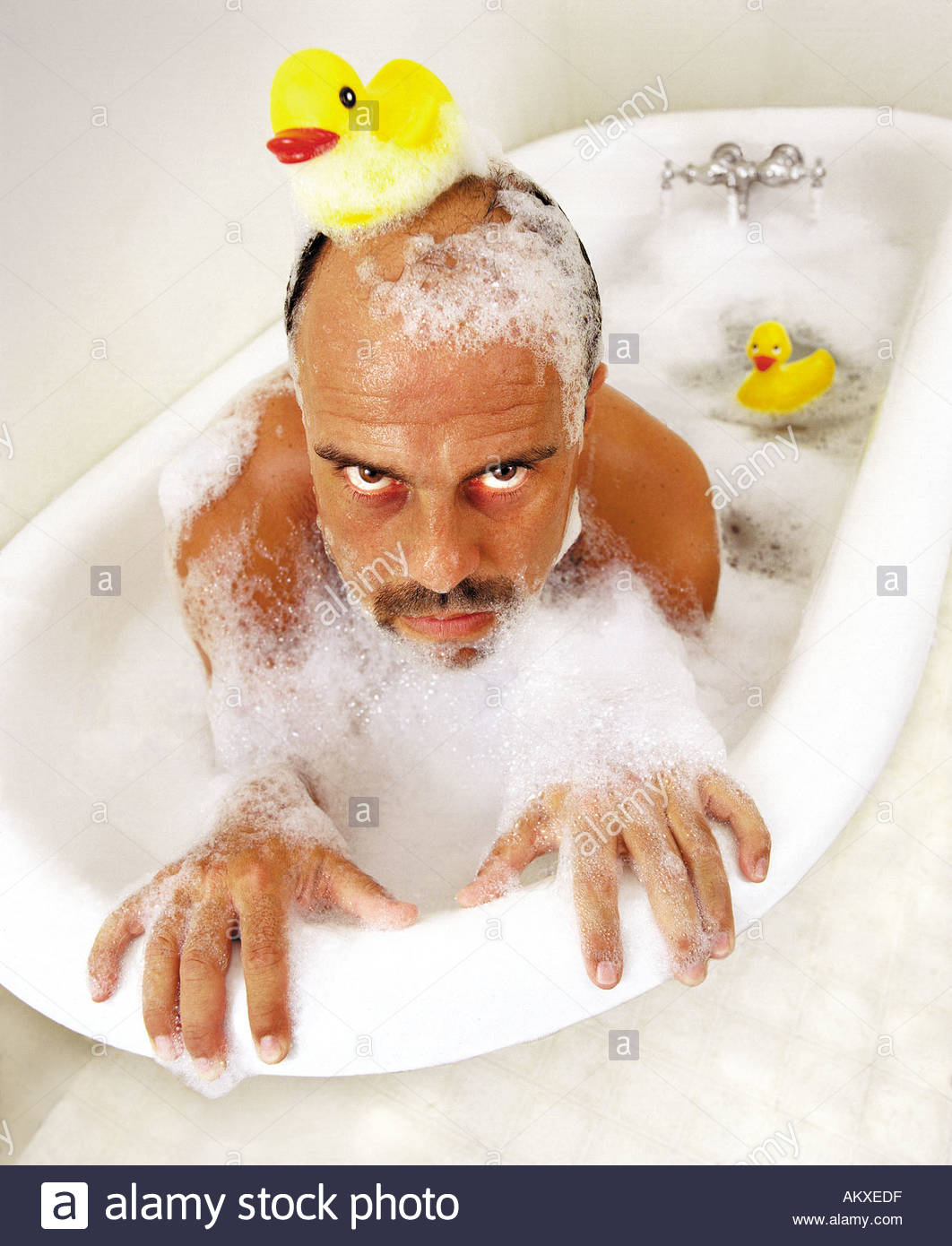 Man in bath tub with bubbles Rubber duck on head rubber duck behind ...