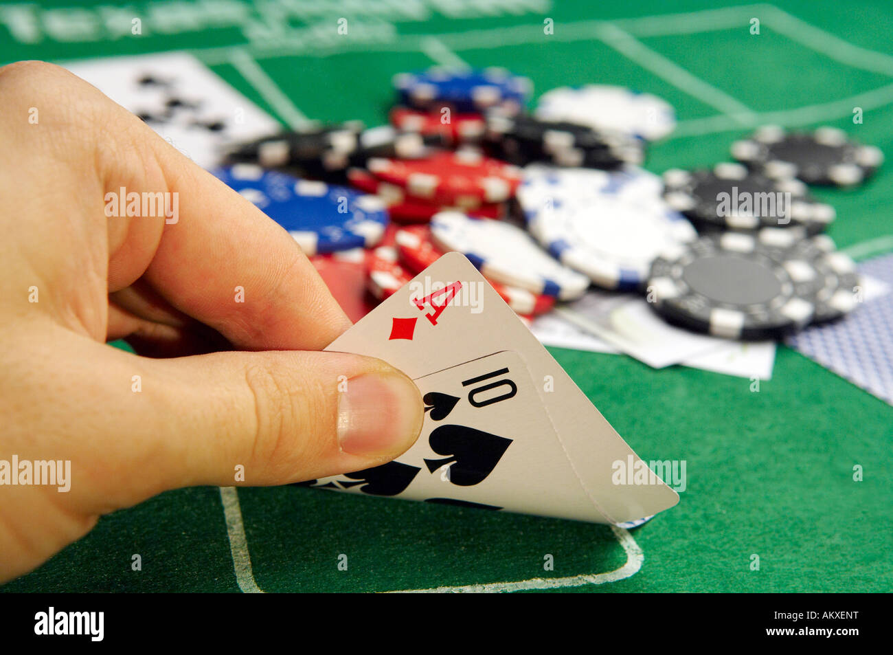 A Poker Player looks at his cards - Stock Image